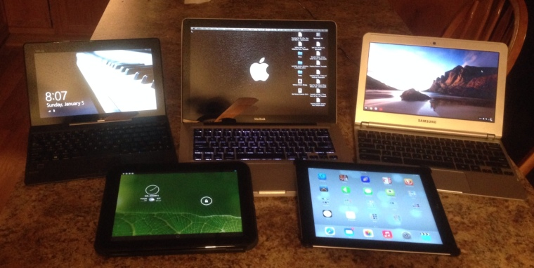 Six operating systems.  Back row: Asus T100 (Windows RT & 8.1), MacBook (OS X 10.9), Chromebook.  Front Row: HP Touchpad (Android 4.3), iPad (iOS 7)